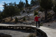 A couple walking along the boardwalk near the travertine terraces at Yellowstone National Park