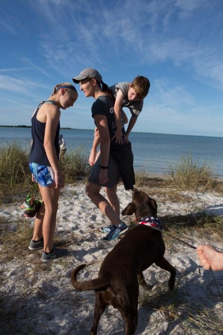 Christine Girtain carries her son, Josh, while her daughter Jaimie smiles after a short visit with Emma and reminiscing about their lab on Honeymoon Island, FL. / ©2016 Audrey Horn / www.usathroughoureyes.com